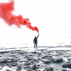 Silhouette einer Person von hinten, in schwarz-weiß, die ein rotes Rauchsignal hält