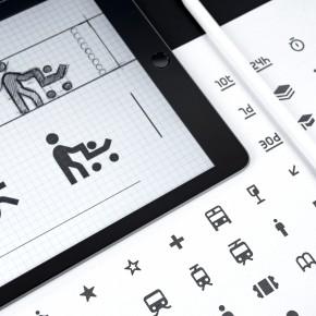 Icons auf einem Tablet und einem Blatt Papier