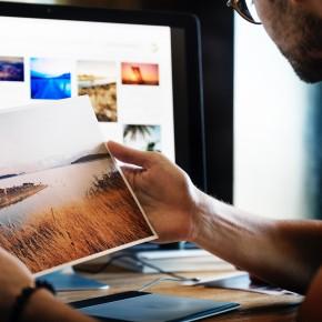Mann betrachtet Ausdruck eines Fotos vor einem Monitor mit weiteren Fotos