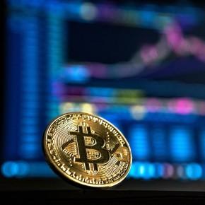 Bitcoin-Münze vor einem verschwommenen Bildschirm