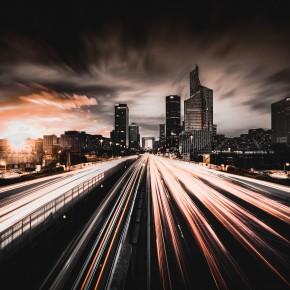 Langzeitaufnahme einer befahrenen Schnellstraße vor der Silhouette einer Großstadt